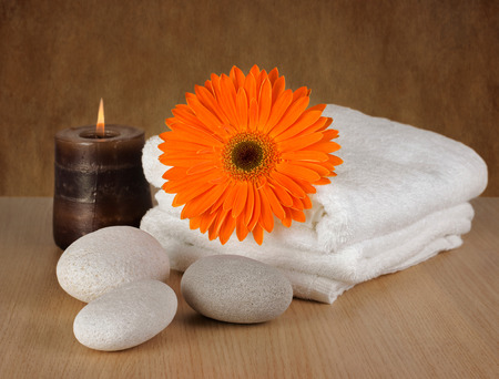 Spa decoration with candle, orange Gerbera daisy and spa stones photo