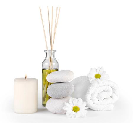 Decorazione Spa con pietre, margherite, candela e una bottiglia con olio da massaggio su un bianco Archivio Fotografico - 27929989