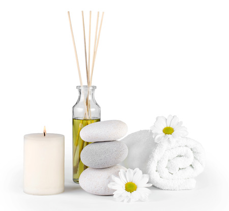 candles spa: Spa decoration with stones, daisies, candle and a bottle with massage oil on a white  Stock Photo