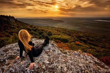 바위의 상단에 여자가 숲을 통해 일몰의보기를 즐긴다