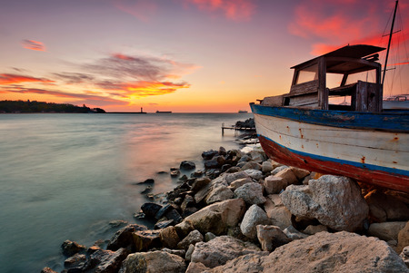 Beautiful sunset view with an old broken boat at the Black sea coast Фото со стока