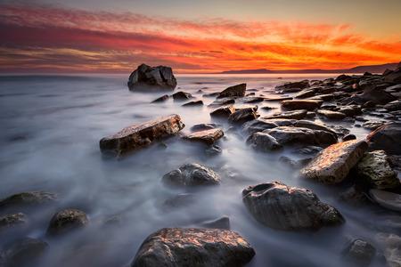 Rocky beach long exposure seascape at sunrise Фото со стока