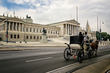 legislator: Carriage with horses in the background of the Neo-Classic temple of parliament government in Vienna, Austria