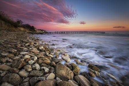 Rocky beach seascape at sunset Фото со стока