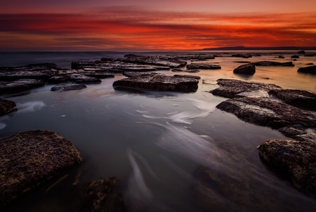 long exposure: Rocky beach long exposure seascape after sunset Stock Photo