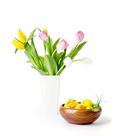 Tulips in a vase and easter eggs in a wooden bowl isolated on white with clipping path photo