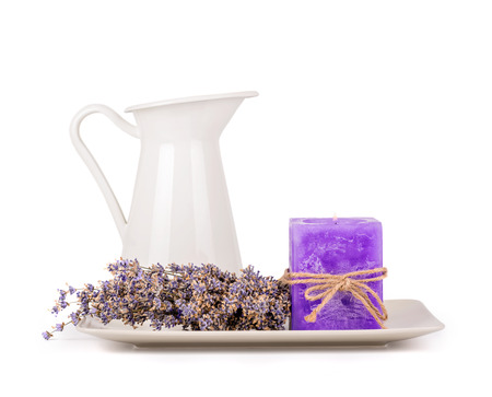 Still life with a white jug and a plate with dry lavender flowers and a lavender candle isolated on white photo