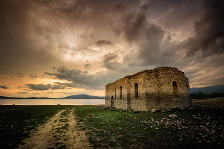 A sunset view of the ruins of an abandoned church situated at the bottom of Zhrebchevo Dam, Bulgaria 版權商用圖片
