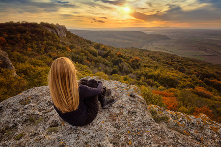 A woman on the top of a rock enjoys the view of sunset over an autumn forest