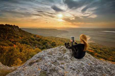 A woman on the top of a rock taking a picture using digital tablet photo