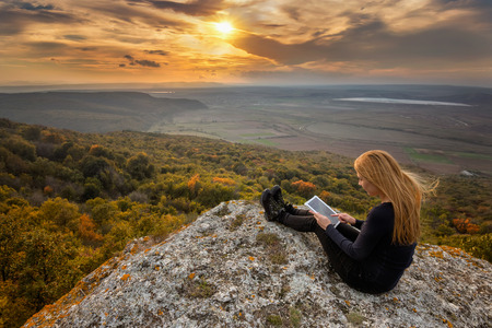 A woman on the top of a rock enjoys the view of sunset and using digital tablet photo