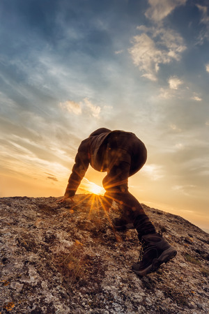 Young woman climbs a rocky hill photo