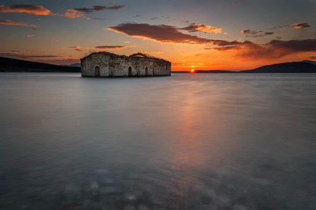 A sunset view of the sunken ruins of an abandoned church situated at the bottom of Zhrebchevo Dam, Bulgaria