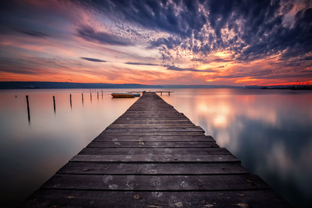 Magnificent long exposure lake sunset with boats and a wooden pier 写真素材