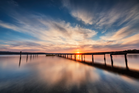 long lake: Magnificent long exposure lake sunset with boat and a wooden pier Stock Photo
