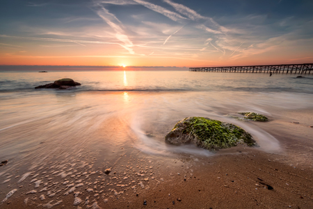 sunny beach: Sea sunrise.  Amazing sea sunrise with slow shutter and waves flowing out.
