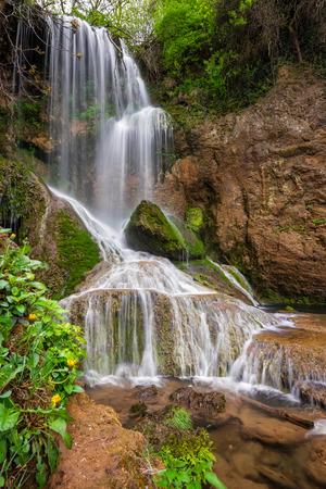 Beautiful view of a waterfall among cliffs in spring time, Krushuna waterfalls in Bulgaria Фото со стока