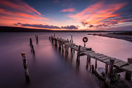 Magnificent long exposure lake sunset with an old wooden pier Stock Photo