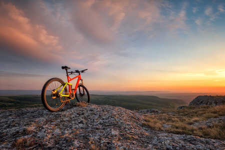 Beautiful sunset view with a mountain bike at the top of a hill Фото со стока