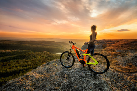 Sunset from the top.  A woman with a bike enjoys the view of sunset over an autumn forest. Фото со стока