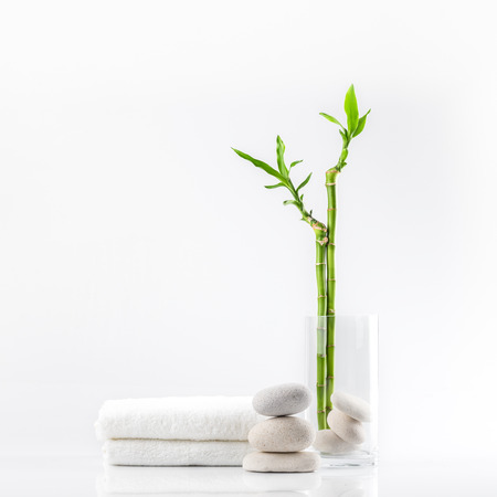 Spa decoration with stones, towel and bamboo in a vase on a white background Фото со стока