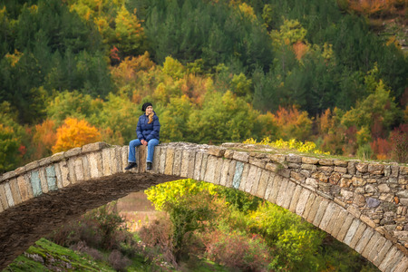 bulgaria girl: Amazing view with old bridge and a woman enjoying the autumn forest in Eastern Rhodopes, Bulgaria