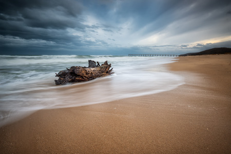 Stormy sea beach with slow shutter and waves flowing out Stock Photo
