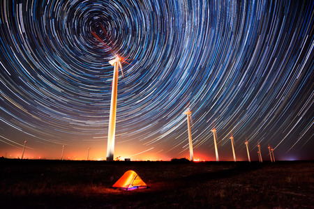 Circles in the night sky.  Long time exposure night landscape with star trails over a wind farm.