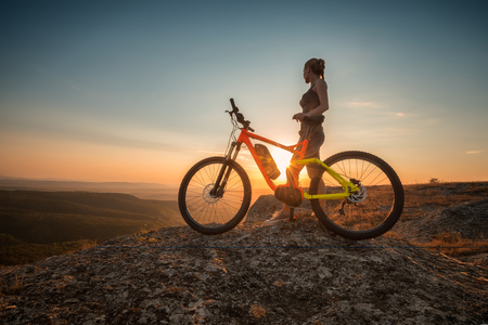 Sunset with a bike.  A woman with a bike enjoys the view of sunset over an autumn forest.