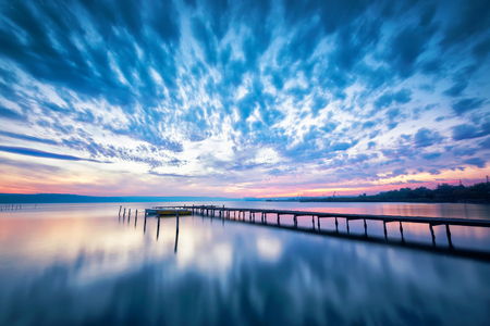 Amazing lake sunset  Magnificent long exposure lake sunset with boat and a wooden pier Фото со стока