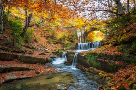 Autumn river with beautiful cascades of water and an old bridge near Sitovo village, Bulgaria Фото со стока