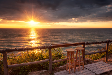 A beautiful sunrise view with first rays and makeshift wooden bar at The Black Sea coast near Varna, Bulgaria