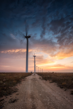 A beautiful sunset view with wind farm along a country road Фото со стока