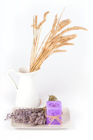 Still life with a white jug and a plate with dry lavender flowers and a lavender candle on white background
