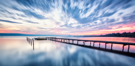 Magnificent long exposure lake sunset with boat and a wooden pier Фото со стока