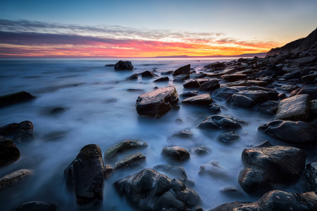 Rocky beach long exposure seascape after sunset Archivio Fotografico - 111094322