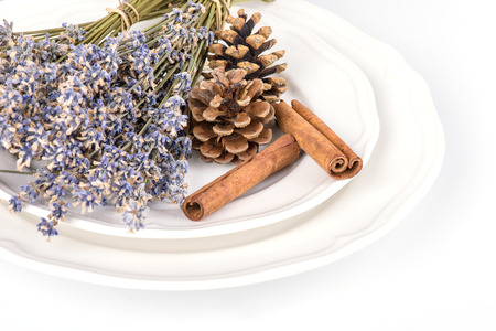 Still life with fir cones, cinnamon and dry lavender on a white plate on white background