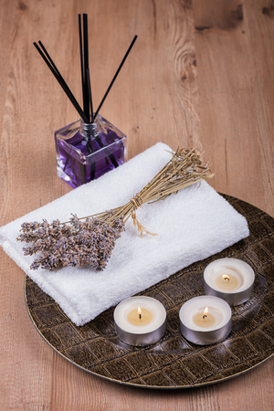 Spa decoration with candles, towels and dry lavender