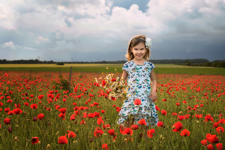 Among the spring field / Beautiful little girl on the  of a poppy field, Bulgaria 写真素材 - 126045590