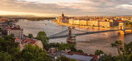 Amazing panorimic view before sunset with the building of Hungarian Parliament in Budapest lit by sun Фото со стока