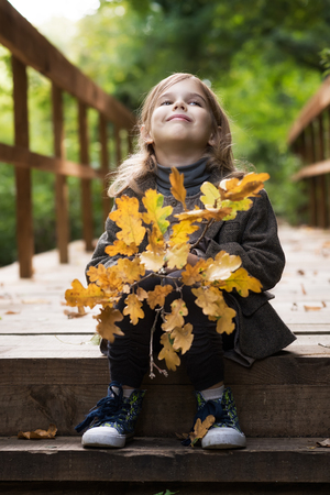 Adorable little girl is playing on an autumn Фото со стока - 126045593