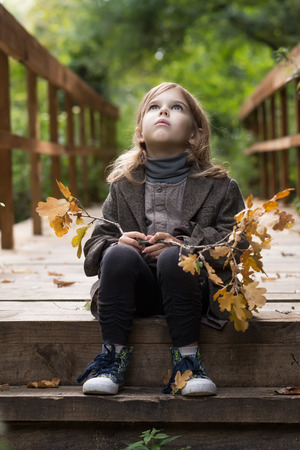 Adorable little girl is playing on an autumn Archivio Fotografico - 126045591