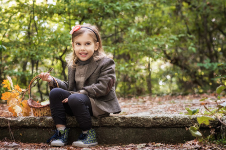 Adorable little girl is walking through an autumn forest Фото со стока