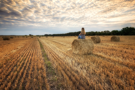Landscape with a woman  in a field full of hay bales before sunset Archivio Fotografico - 118435533