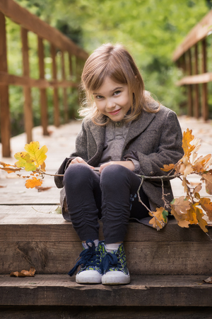 Adorable little girl is playing on an autumn