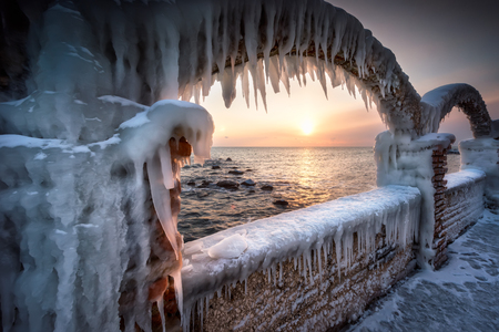 Magnificent morning view with an ice-covered pendant fence at the  Black sea coast