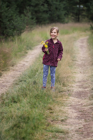Lovely little girl walking along a forest path Фото со стока - 126045599