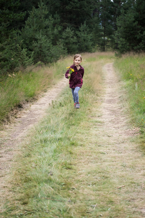 Lovely little girl running along a forest path