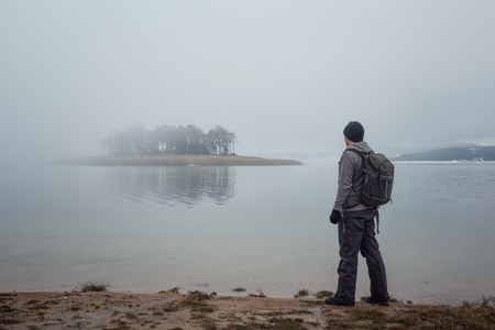 Rear view of a man with a backpack hiking in the winter Rhodopi Mountains in Bulgaria and enjoys the view of the lake and covered by fog islet Фото со стока