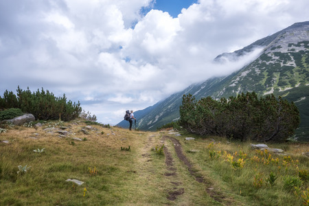 Rear view of a man with a backpack hiking in the summer mountain